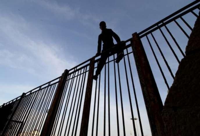Un jeune Marocain tente de franchir l'enceinte du port de Melilla, l'enclave espagnole dans le nord du Maroc, en mai 2017.