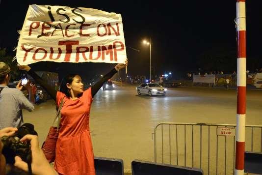 La musicienne et dissidente Mai Khoi brandissant une pancarte à l'attention du président des Etats-Unis, Donald Trump, à Hanoï, le 11 novembre.