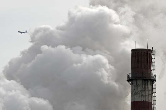 FILE - In this Feb. 28, 2017 file photo, a passenger airplane flies behind steam and white smoke emitted from a coal-fired power plant in Beijing. On Monday, Nov. 13, 2017, scientists projected that global carbon pollution has risen in 2017 after three straight years when the heat-trapping gas didn't go up at all. (AP Photo/Andy Wong, File)