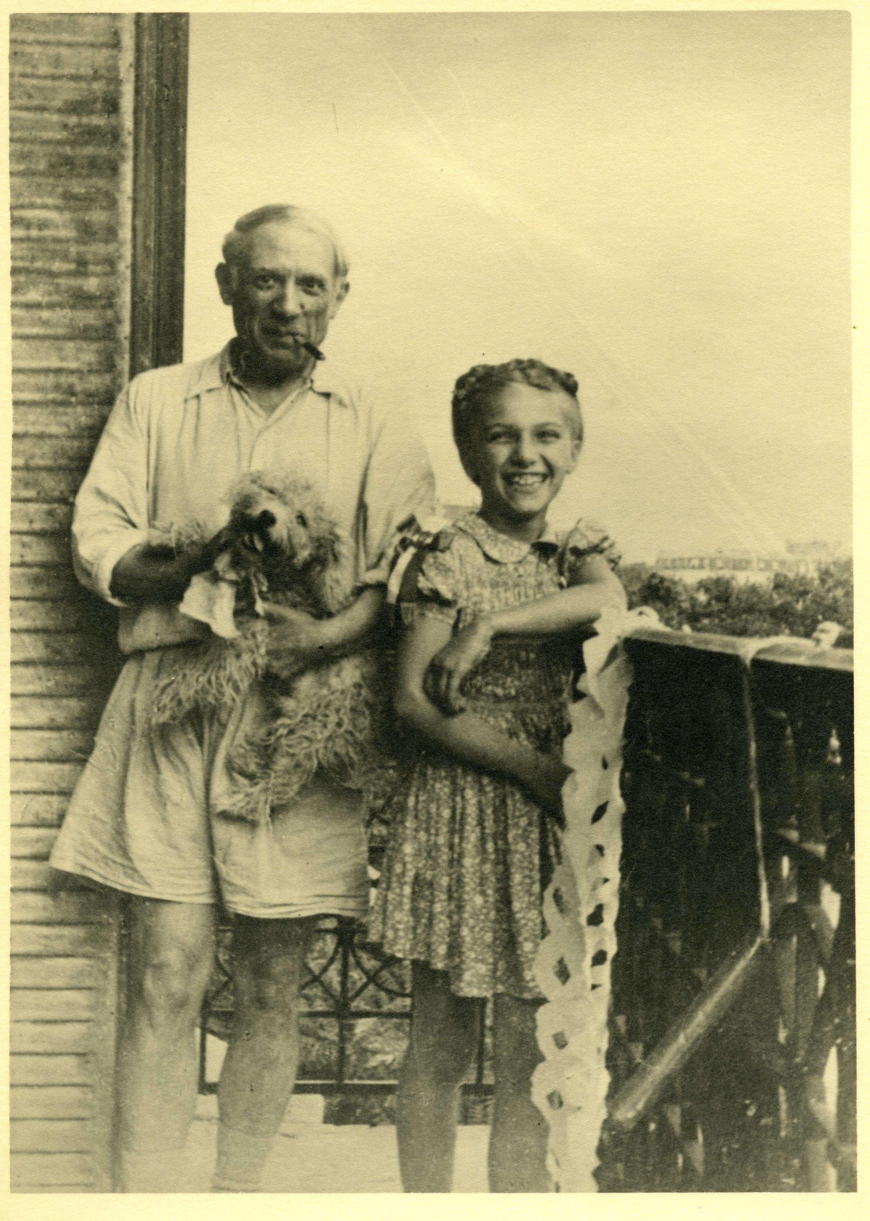 """«Ce cliché, probablement pris par Marie-Thérèse, immortalise un jour symbolique, le 25 août 1944, alors que Paris est enfin libérée, sur le balcon de l'appartement du boulevard Henri IV. Malgré sa liaison avec Dora Maar, Picasso venait souvent rendre visite à Marie-Thérèse et Maya, soucieux de préserver sa vie de famille et de passer du temps avec sa fille. Un mois plus tôt, il écrivait à Marie-Thérèse à l'occasion de son anniversaire : """"MTW aujourd'hui 13 juillet 1944 est le 17e anniversaire de ta naissance en moi, et le double de ta naissance à toi dans ce monde où, t'ayant rencontré, j'ai commencé à vivre"""", un précieux témoignage de l'amour qu'il lui portait.»"""