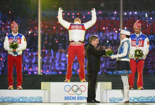 International Olympic Committee (IOC) President Thomas Bach (front) awards (From L) Russia's silver medalist Maxim Vyleghzanin, Russia's gold medalist Alexander Legkov and Russia's bronze medalist Ilia Chernousov on the podium of the the Men's Cross-Country Skiing 50km Mass Start at the Closing Ceremony of the Sochi Winter Olympic. The first two have since lost their medal due to suspicions of doping.