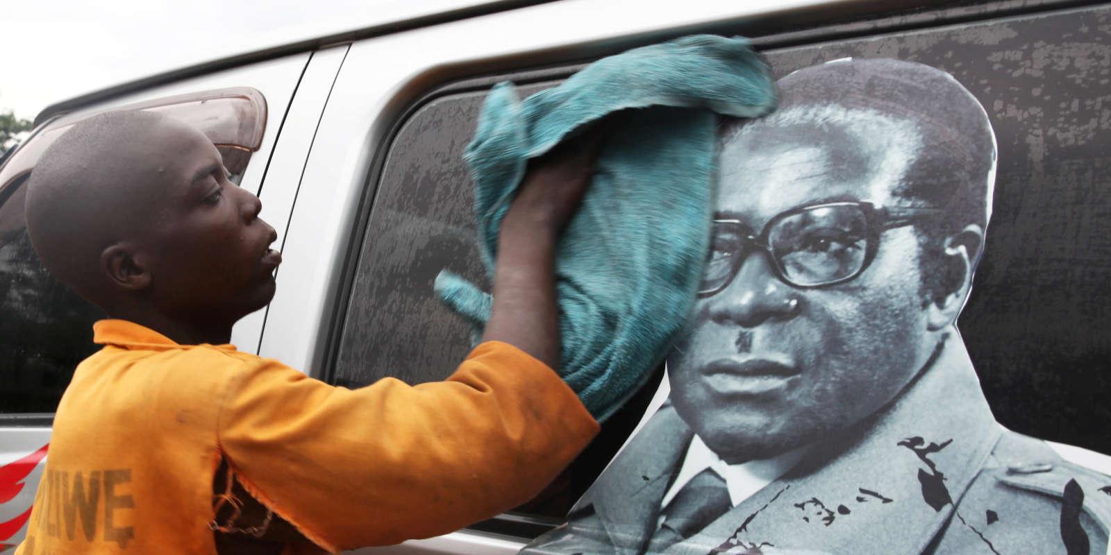 Un homme nettoie un minibus sur lequel figure une image du President Robert Mugabe, à Harare le 15 novembre.