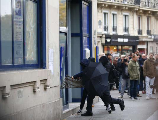 Des individus attaquent un distributeur de billets de la banque LCL en marge de la manifestation du 16 novembre à Paris.