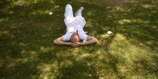 A reveler takes a nap in a park during the San Fermin Festival in Pamplona, northern Spain, on July 12, 2015. The festival is a symbol of Spanish culture that attracts thousands of tourists to watch the bull runs despite heavy condemnation from animal rights groups. AFP PHOTO/ MIGUEL RIOPA / AFP PHOTO / MIGUEL RIOPA
