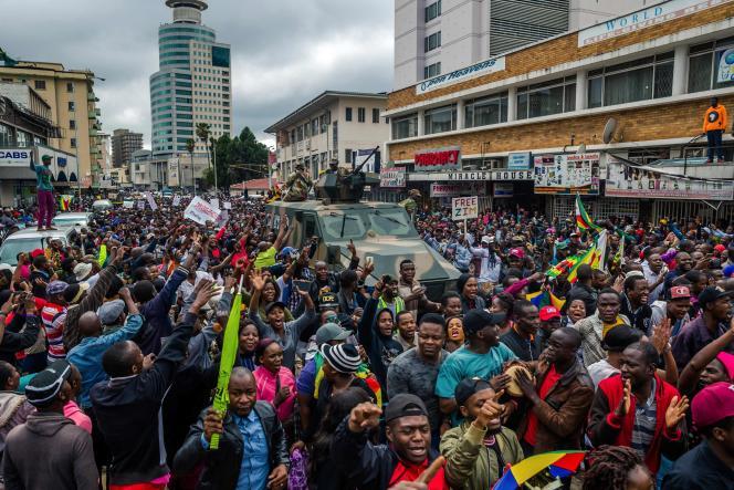 Les manifestants acclament un véhicule des forces de défense zimbabwéennes, à Harare, le 18 novembre.