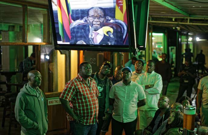 Des Zimbabwéens écoutent Robert Mugabe lors de son allocution télévisée, dans un bar d'Harare, le 19 novembre.