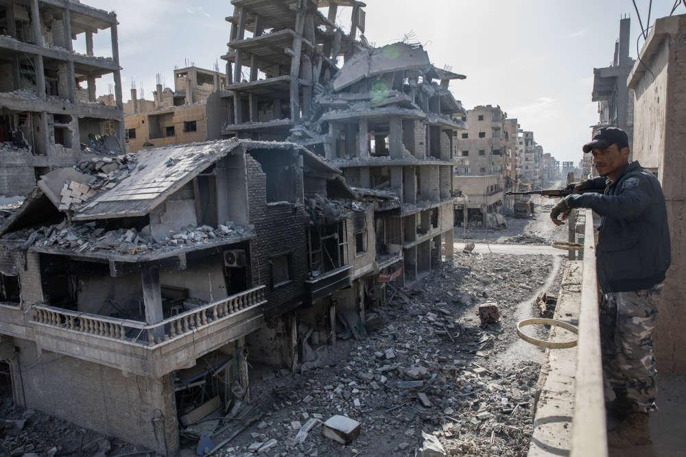 Basel, le jeune soldat FDS de 33 ans, observe la vue du toit de la maison d'Ibrahim.