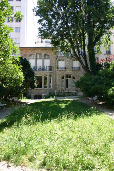 Vue de la façade qui donne sur un jardin de 800m2 : elle est faite de moellons redressés et de briques.