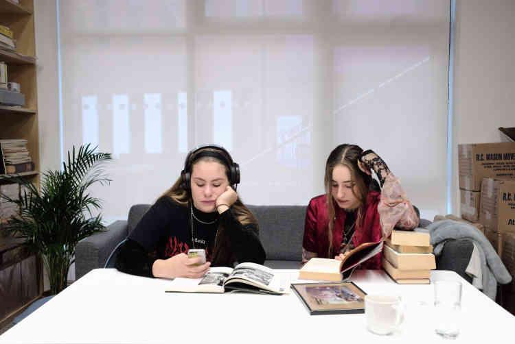 Les sœurs McMullen de Bristol sont plongées dans les livres de la collection de Martin Parr en attendant de poser avec leurs parents et leurs beagles devant le photographe.