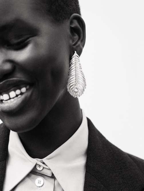 Pendant d'oreille Plume de Paon en or blanc pavé de diamants, Boucheron. Chemise en cuir blanc avec col oversize et veste en laine, Céline.
