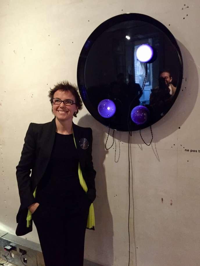 Constance Guisset, au musée des Arts décoratifs, de Paris, devantCoulisse,un miroir noir d'où coulent des planètes de verre soufflé(édition limitée à 25 exemplaires pour Cat-Berro Galerie, 2012).