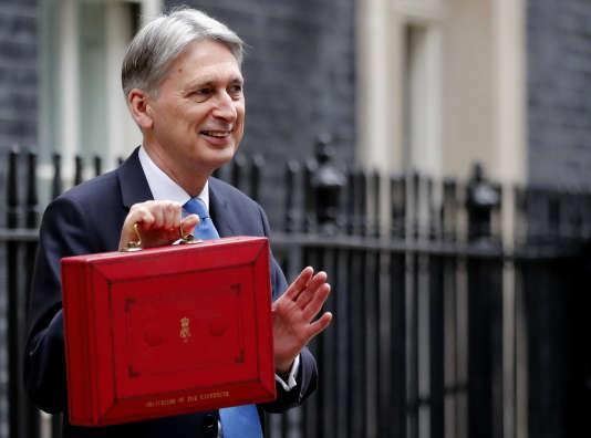Le chancelier de l'Echiquier britannique, Philip Hammond, pose pour les médias devant sa résidence officielle du 11 Downing Street, muni de la traditionnelle mallette rouge contenant son discours sur le budget, à Londres, le 22 novembre.