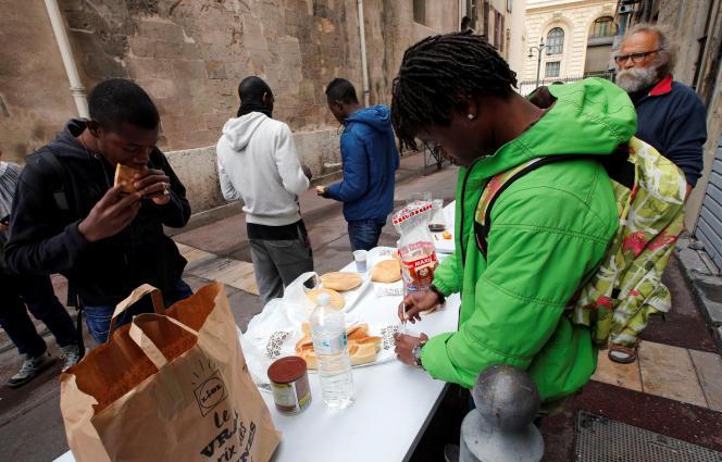 Des bénévoles distribuent de la nourriture à des migrants qui occupent l'église Saint-Ferréol, à Marseille, le 23 novembre.