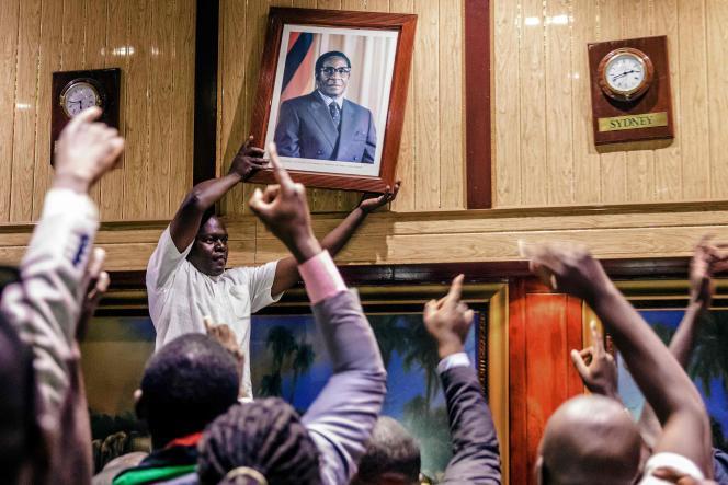 Le portrait officiel de Robert Mugabe est décroché après sa démission, au Centre international de conférence de Harare, le 21 novembre.