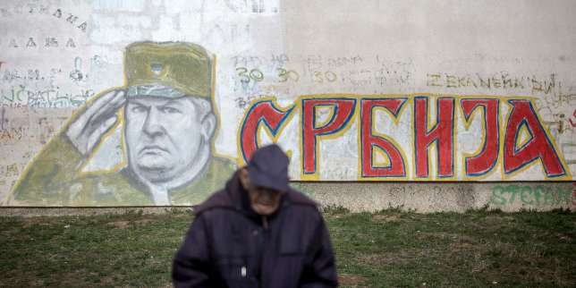 """TOPSHOT - A man stands in front of a graffiti depicting former Bosnian Serb commander Ratko Mladic and reading """"Serbia"""" written in Cyrillic, painted on a wall in Belgrade on Nocember 22, 2017. Ratko Mladic, who was convicted of genocide on November 22, 2017, believed himself to be a crusading defender of the Serbs but was dubbed the """"Butcher of Bosnia"""" for mass slaughter at the hands of his forces. / AFP / OLIVER BUNIC"""