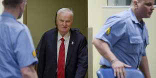 """TOPSHOT - Bosnian Serb military chief Ratko Mladic (C) smiles as he enters the International Criminal Tribunal for the former Yugoslavia (ICTY), on November 22, 2017, to hear the verdict in his genocide trial. Dubbed """"The Butcher of Bosnia,"""" Mladic's trial is the last before the ICTY, and the judgement has been long awaited by tens of thousands of victims across the bitterly-divided region, seeking to close a chapter in the brutal 1990s Balkans conflicts.  / AFP / POOL / Peter Dejong"""