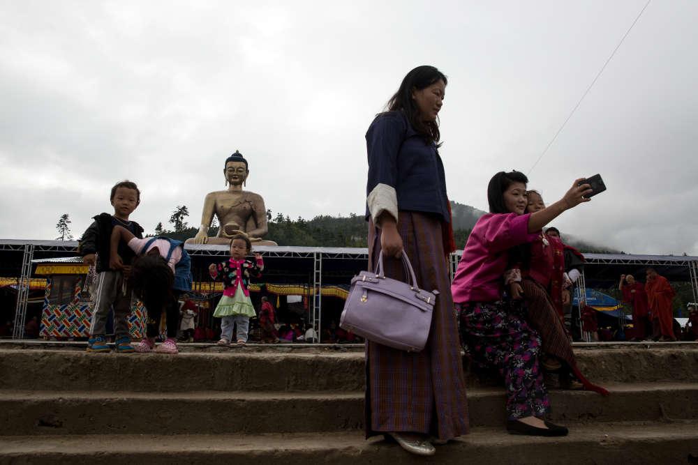 Touristes et moines bouddhistes au pied du grand Bouddha Dordemma, à Thimphou.