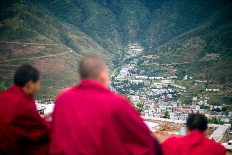 Des moines bouddhistes font une halte sur l'un des chemins montagneux surplombantla capitale du Bhoutan, Thimphou.