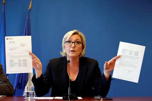 Marine Le Pen brandit les lettres envoyées par la Société générale et HSBC, le 22 novembre, au quartier général du FN à Sarcelles.