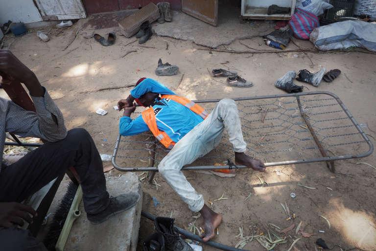 """Dans un ghetto pour les collecteurs de déchets .homme originaire du Niger rentre à peine de sa journée de travail, il s'effondre de fatigue. Il attend d'avoir suffisament d'argent pour rentrer dans son pays d'origine. Certains de ces hommes n'ont plus de salaire depuis 6 mois : """"la Libye c'est fini, il n'y a plus d'argent ici !"""""""