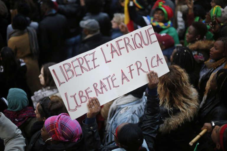 Un manifestant brandit une pancarte, lors d'un rassemblement contre l'esclavage, devant l'ambassade de Libye à Paris, le 24novembre 2017.