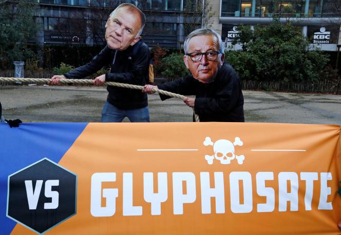 Des manifestants protestent, le 27 novembre 2017 à Bruxelles, contre le commissaire européen chargé de la santé et de la sécurité alimentaire de la Commission européenne, Vytenis Andriukaitis, et Jean-Claude Juncker, le président de la Commission européenne, à propos de la décision de l'UE d'étendre la licence du glyphosate pour encore cinq ans.