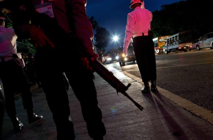 Un officier birman face au convoi transportant le chef de l'armée, le général Min Aung Hlaing, le 27novembre à Rangoun.