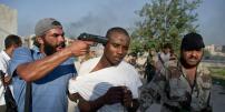 Cette photo de Rémi Ochlik a été prise le 25 août 2011. La légende d'origine est la suivante :« Des combattants rebels à Abu Slim s'opposent aux dernières résistances des forces loyales à Khadafi. Ils ont capturé des Africains soupçonnés d'être des mercenaires de Khadafi.»