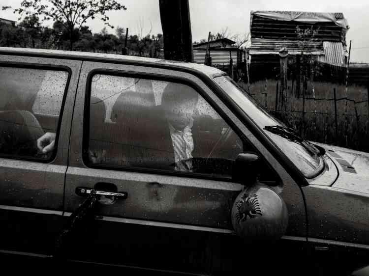 Un homme dans une voiture dans une banlieue de Tirana. Lessymboles nationaux, comme l'aigle à deux têtes, qui apparaît ici sur un ballon accroché au rétroviseur, sont utilisés couramment par les Albanais.