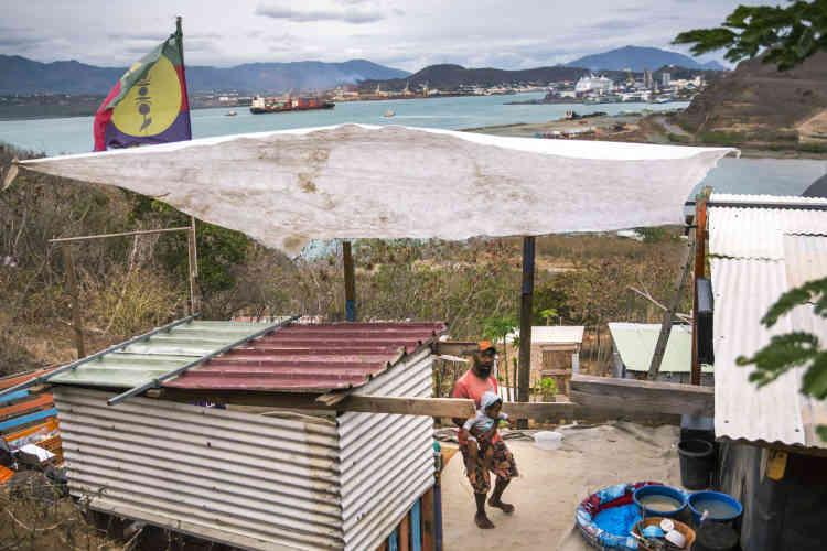 Dans un bidonville de Nouméa, le 22 novembre. La bâtisse est surmontée du drapeau kanak. Faute de logement, les calédoniens de province, pour la plupart kanaks, cherchant du travail en ville, ont construit des cabanes avec des matériaux de récupération sur des terrains inoccupés de la presqu'île de Nouville face au centre-ville de Nouméa. Les squats du grand Nouméa accueilleraient aujourd'hui plus de 10 000 personnes dans une agglomération d'environ 180 000 habitants.