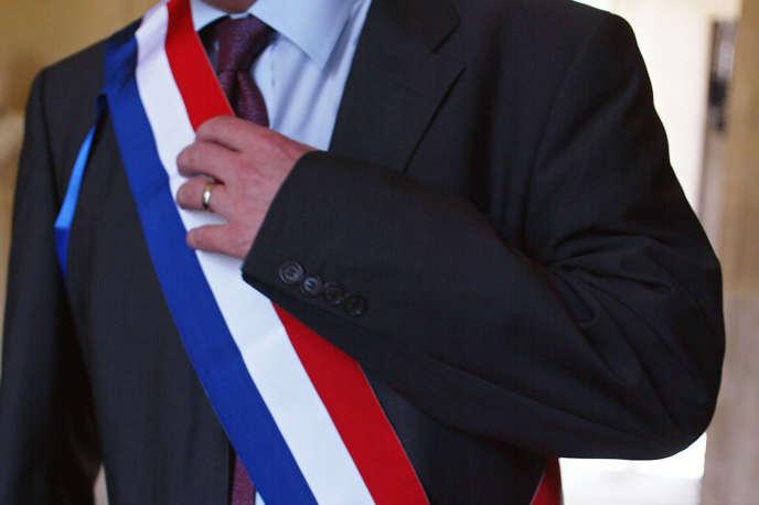 Un député vêtu de son écharpe tricolore, au Palais-Bourbon à Paris.