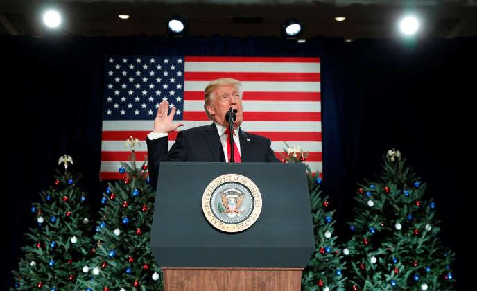 Donald Trump et en arrière plan des sapins de Noël aux boules bleus, blancs, rouges, surmontés de l'aigle américain.