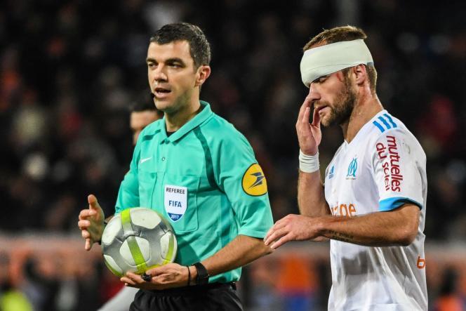 Frank Schneider, avec un ballon, et Valère Germain, en sang avec un bandage, échangent leurs points de vue lors du match Montpellier-Marseille, le 3 décembre.