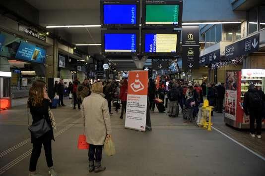 Des passagers regardent les écrans des départs et des arrivées, vides, à la gare Montparnasse, à Paris, le 3 décembre 2017.