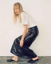 Chemise à manches ballon en popeline de coton, jupe longue en python, Azzedine Alaïa. Chaussons en cuir, Charvet.