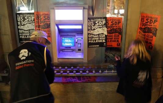 Des militants de la Fondation Abbé Pierre placardent des affiches sur une agence du Crédit lyonnais, le 6 décembre 2017 à Paris.