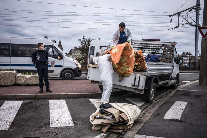 Des agents de la ville de Calais récupèrent les biens des migrants, le 5 décembre. OLIVIER PAPEGNIES/COLLECTIF HUMA POUR « LE MONDE »
