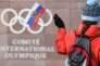 A supporter waves a Russian flag in front of the logo of the International Olympic Committee (IOC) at their headquarters on December 5, 2017 in Pully near Lausanne. The International Olympic Committee meets to decide whether to bar Russia from the 2018 Winter Olympics for doping violations, in one of the weightiest decisions ever faced by the Olympic movement. - / AFP / Fabrice COFFRINI