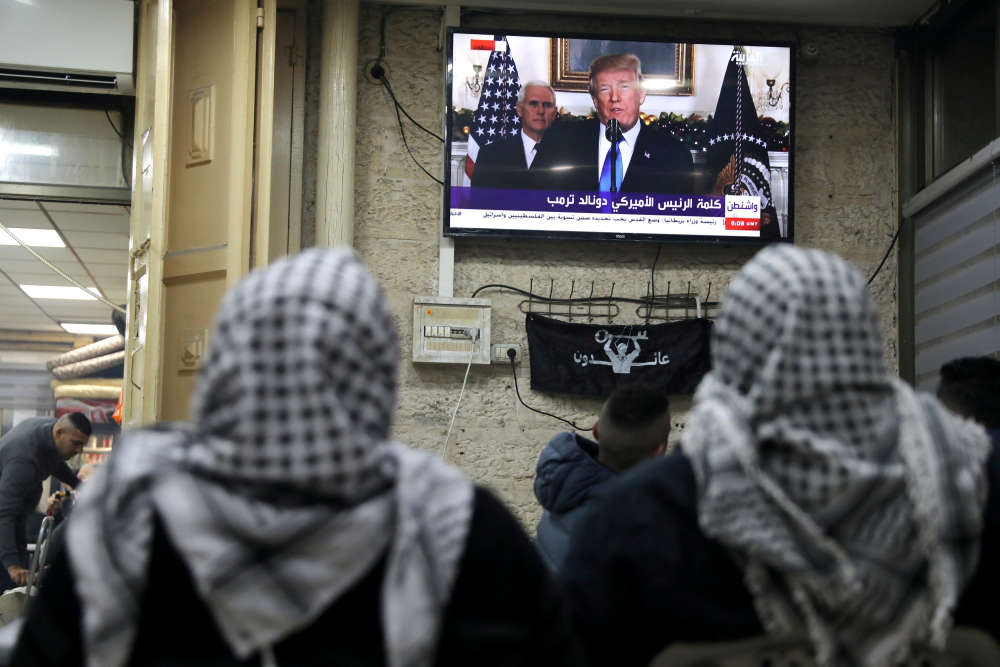 Des Palestiniens regardent Donald Trump annoncer l'intention des Etats-Unis de reconnaître Jérusalem comme la capitale d'Israël, dans la vieille ville de Jérusalem, le 6 décembre.