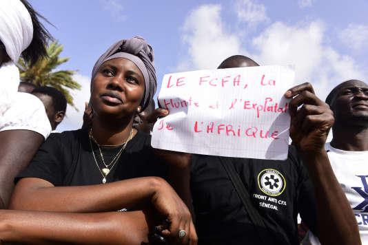 """«Partagée par quinze Etats africains et garantie par le Trésor français, le franc CFA est vilipendé par ses contempteurs comme un """"symbole de la servitude"""", un ultime avatar de la Françafrique, plus de cinquante ans après les indépendances. » (Photo : Manifestation contre le franc CFA, sur la place de l'Obélisque, à Dakar, le 16 septembre)."""