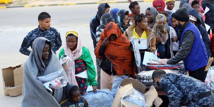 Des migrants subsahariens lors d'une distribution de vêtements dans un camp de rétention de la banlieue de Tadjourah, à l'est de Tripoli, en Libye, le 5 décembre 2017.