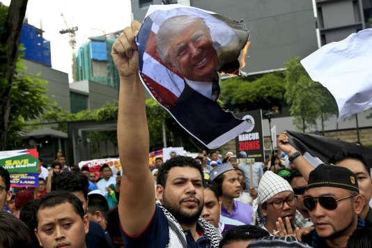 Des manifestants brûlent une photographie de Donald Trump, à Kuala Lumpur.