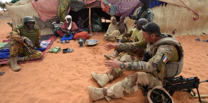 Un soldat français de l'opération Barkhane, accompagné d'un militaire malien, échangeant avec une famille touarègue à Timbamogoye, le 10 mars 2016.