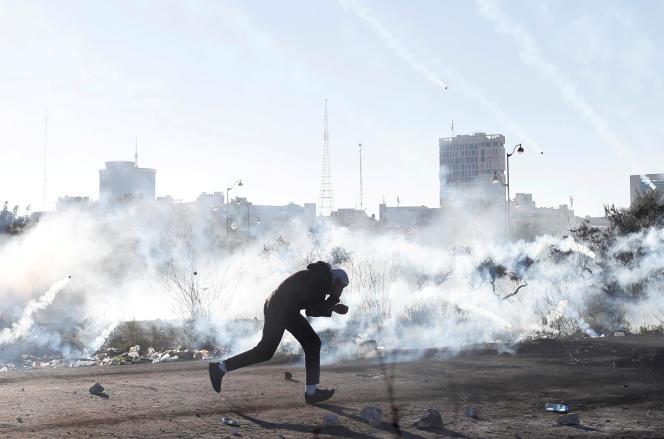Un manifestant palestinien se replie pour échapper aux gaz lacrimogènes, à Ramallah dans les territoires occupés, le 8 décembre.