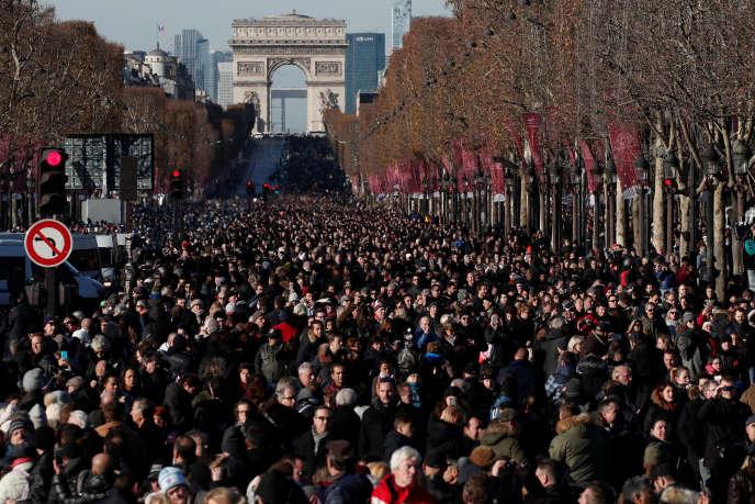 Sur les Champs Elysée, la foule derrière le cortège funéraire de Johnny Hallyday, le 9 décembre.