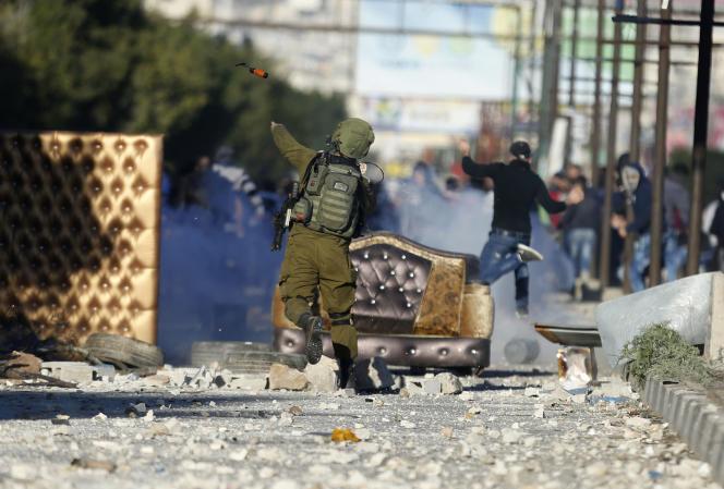 Un soldat israélien lance une grenade assourdissante en direction des émeutiers palestiniens, à Naplouse, le 8 décembre.