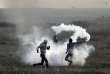 """Palestinian protesters throw back a teargas canister fired by Israeli troops during clashes on the Israeli border with Gaza, Saturday, Dec. 9, 2017. Protests and demonstrations continued across the West Bank and Gaza on Saturday on the third and final so-called Palestinian """"day of rage"""" following Trump's announcement. Along the border with the Gaza Strip, some 450 Palestinians clashed with Israeli troops at eight main locations. About 20 were lightly wounded. (AP Photo/ Khalil Hamra)"""