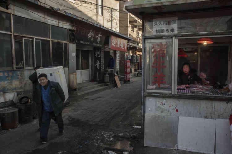 Dans le «village urbain» de Taozhuang, un homme porte une machine à laver appartenant à une famille d'ouvriers migrants obligée de quitter les lieux.