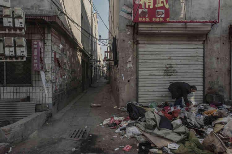 Dans une rue désertée du «village urbain» de Xinjian, un collecteur d'ordures fouille dans les détritus laissés par les habitants partis à la hâte.