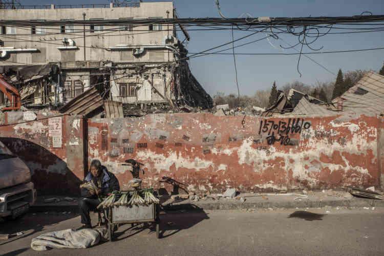 Un homme vend des poireaux aux pieds de ruines du «village urbain» de Taozhuang.